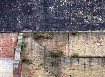 full frame image of a very large old brick wall with many patched and repaired sections stains weeds and black painted area
