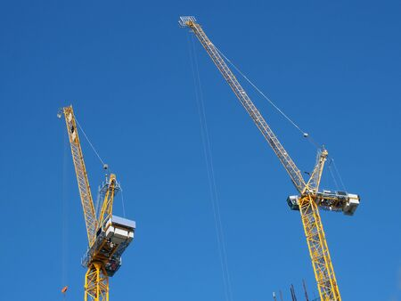 Photo pour two tall yellow tower cranes working on a construction site against a blue sky - image libre de droit