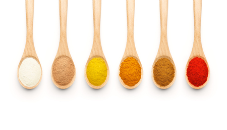 Wooden Spoon filled with colorful spices on white background