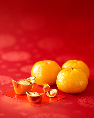 Photo pour Chinese New Year - Mandarin orange, gold sycee (Foreign text means wealth) and red packet - image libre de droit