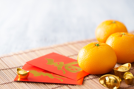 Chinese New Year - Mandarin orange, gold sycee (Foreign text means wealth) and red packet (Foreign text means spring season) on white painted wood table