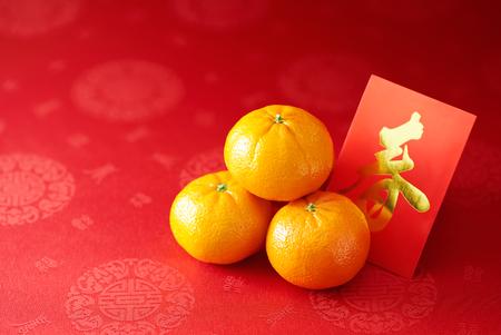 Foto de Chinese New Year - Mandarin orange and red packet (Foreign text means spring season) - Imagen libre de derechos