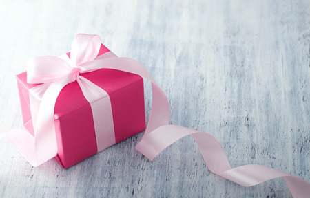 Photo for Pink gift box with ribbon on white painted wood background - Royalty Free Image