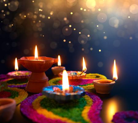 Diya lamps lit on colorful rangoli during diwali celebration