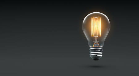 Foto de Glowing Edison light bulb on dark - Imagen libre de derechos