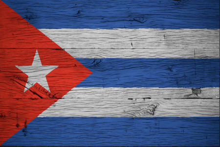 Cuba national flag painted on old oak wood. Painting is colorful on planks of old train carriage.