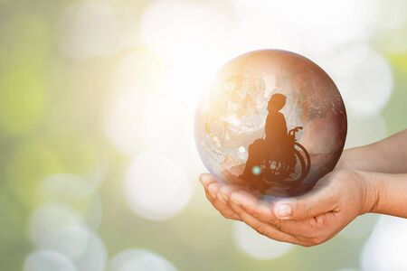 Photo for Disabled person on wheelchair in earth holding in human hands towards goals city across active work. International Disability Day or Handicapped Paralympics. Autistic Awareness Day and health concept. - Royalty Free Image