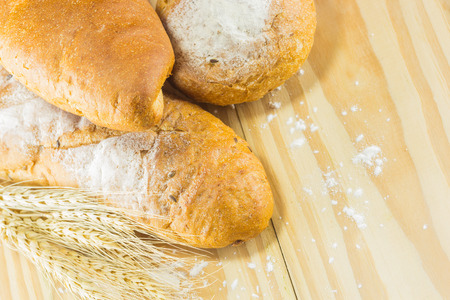bread and wheat on the wood background, warm toning, selective focus