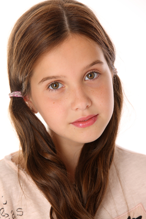 Photo for Portrait of a pretty young teenage girl close-up. Adorable preteen with dark hair and charming face on a white background. The image of children's summer fashion. - Royalty Free Image