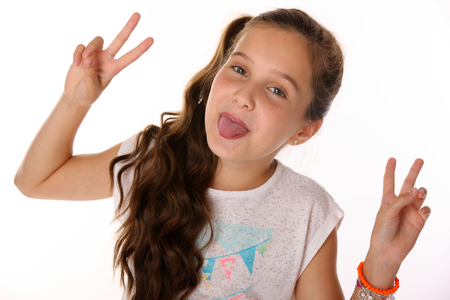 Portrait of beautiful cheerful brunette young teen girl builds a smiley face ape. The child playing tricks and shows tongue. Laughing preteen is an image of children's summer fashion.