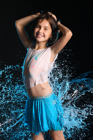 Portrait of a charming slender child standing with wet body and smile. Pretty young beautiful girl with bare belly in wet clothes and skirt. Attractive happy teenager in splashes of water.