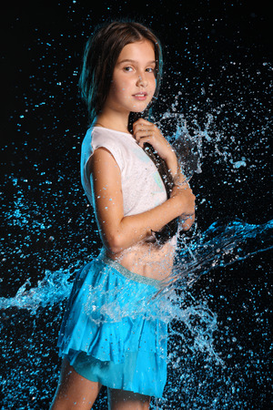 Portrait of a charming child standing with wet slender body. Pretty young beautiful girl with bare belly in wet clothes and skirt. Attractive young teenager in splashes of water.