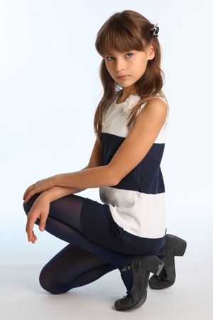 Slender beautiful girl in a striped dress sat on her knee. Charming graceful and attractive child in blue tights. Young schoolgirl-model 9 years old.