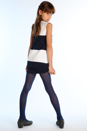 Beautiful girl in a striped dress poses with her back turned. Elegant attractive child with a slender body and long legs in blue tights. The young schoolgirl is 9 years old.