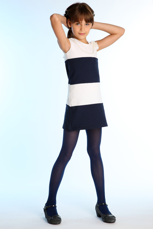 Beautiful girl in a striped dress is standing at full length. Elegant attractive child with a slender body and long legs in blue tights. The young schoolgirl is 9 years old.