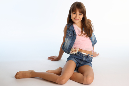 Beautiful girl in a denim shorts is resting on the floor barefoot. Elegant attractive child with a slender body and bare long legs. The young schoolgirl is 9 years old.の写真素材