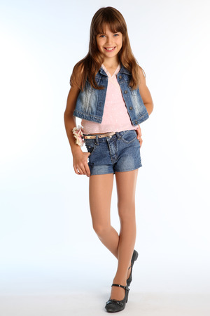 Beautiful girl in a denim shorts is standing at full length. Elegant attractive child with a slender body and long legs in pantyhose. The young schoolgirl is 9 years old.の写真素材