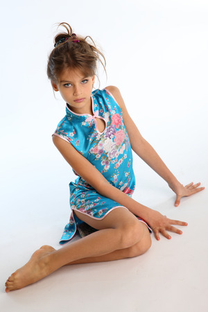 Beautiful girl in an asian blue dress is sitting barefoot. Elegant attractive child with a slender body and bare long legs. The young model 9 years old in fashion style.の写真素材