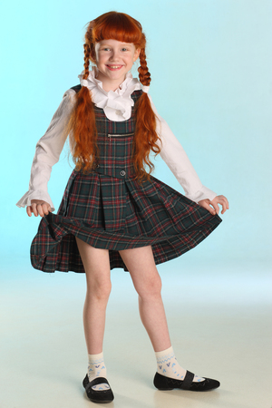 Beautiful happy little redhead girl shows her school uniform at full length. Elegant attractive child with a slender body and slim bare legs. The young schoolgirl is 8 years old.