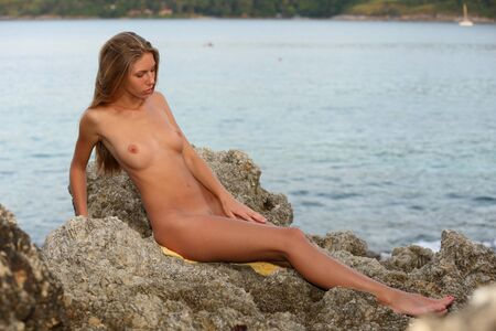 Photo pour Amazingly beautiful young adult tanned and completely nude girl sitting on a rocky seashore against the background of the evening light blue water. - image libre de droit