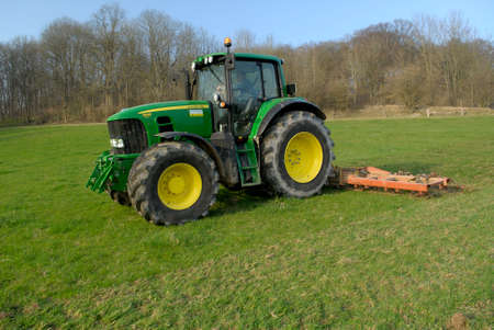 Normandy, France, March 2012. Soil is worked with surface tools. Farmer preparing his meadow using a harrow.