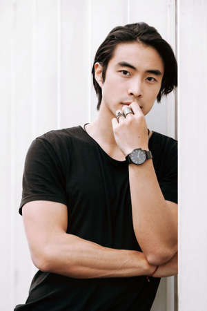 Photo pour Asian male model posing arms crossed thinking, hand touches face, confident look, leaning against the white wall, long dark haircut, wearing black t-shirt, model test shoot - image libre de droit