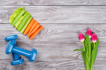 Photo for Spring flatlay sports composition with celery an carrots blue dumbbells and tulips on gray wooden background. Concept healthy lifestyle, sport and diet in spring. Top view - Royalty Free Image