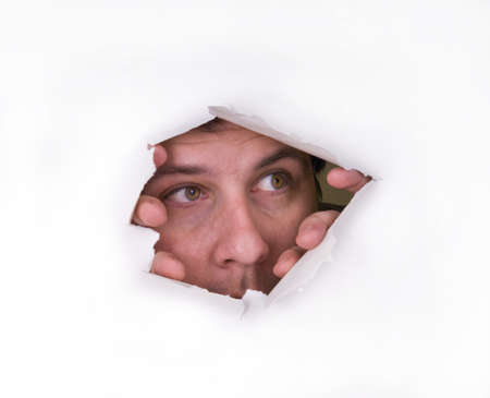 Photo for A man looks through a hole in the paper - Royalty Free Image