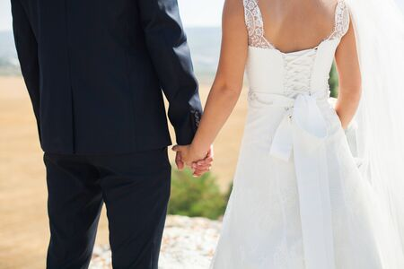 Photo pour Bride and groom walking together holding their hands - image libre de droit