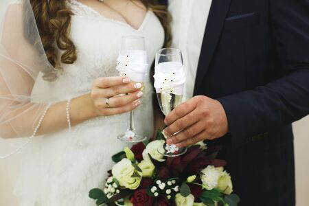 Foto für bride and groom holding beautifully decorated wedding glasses with champaign - Lizenzfreies Bild