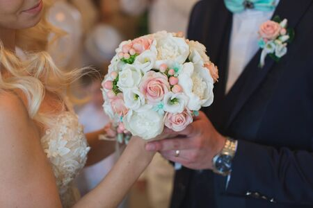 Photo for Groom in a suit gives the bride a white and peach wedding bouquet - Royalty Free Image
