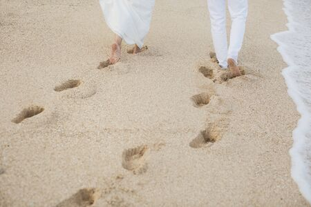 Photo pour The bride and groom walk hand in the sand. footprints in the sand near the ocean. - image libre de droit