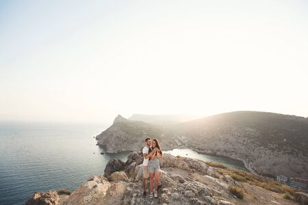 Photo for Lovers, guy and girl, on the edge of the cliff against the backdrop of mountains and ocean - Royalty Free Image
