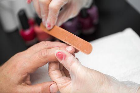 Foto de Girl manicurist doing manicure for man in beauty salon. - Imagen libre de derechos