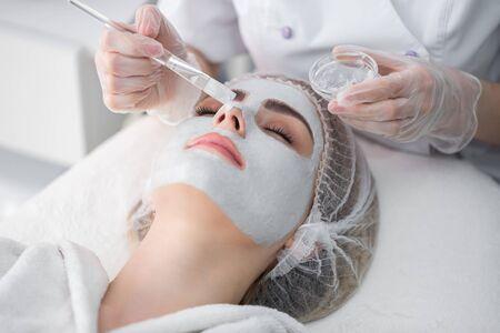 Photo pour Face peeling mask, spa beauty treatment, skincare. Woman getting facial care by beautician at spa salon. - image libre de droit