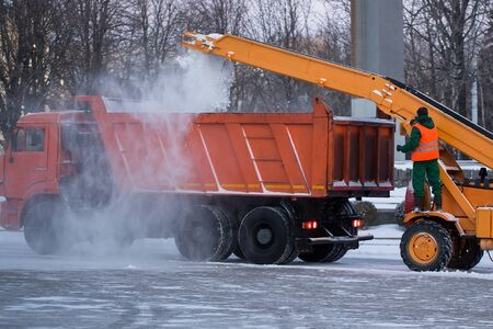 Tractor cleaning the road from the snow. Excavator cleans the streets of large amounts of snow in city. Workers sweep snow from road in winter, Cleaning road from snow storm