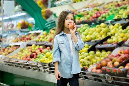 Foto für Little girl choosing a bio apple in a store. - Lizenzfreies Bild