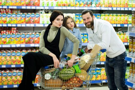Beautiful young parents and their cute little daughter are smiling while choosing food in the supermarket. Father pushes the shopping cart while the girls sit there.