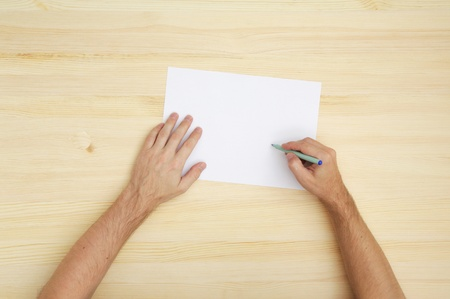 man writing on the paper, top view