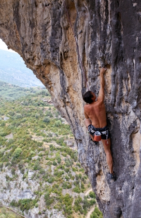 Rock climber battles his way up an arch in Rodellar Canyon, Spain