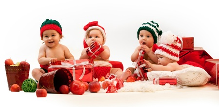 Photo pour Four babies in xmas costumes playing among gifts - image libre de droit