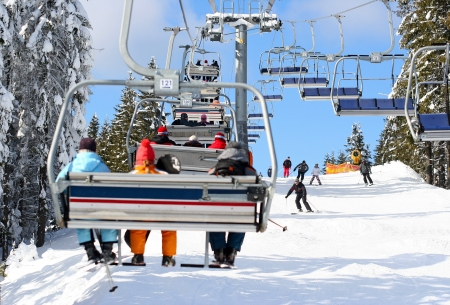 Skiers go on the lift on mountain in Bukovel, Ukraine