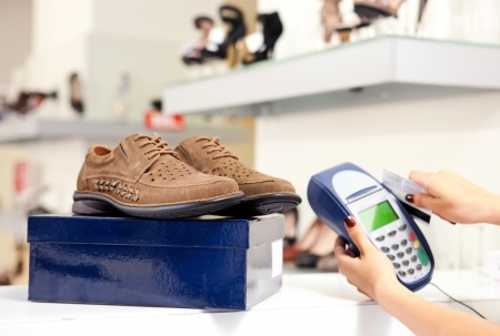Moment of payment using credit card terminal in shoe store  Selective focus on pair of male shoes on top of box
