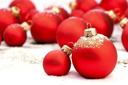 Photo pour Red Christmas baubles on snow  - image libre de droit