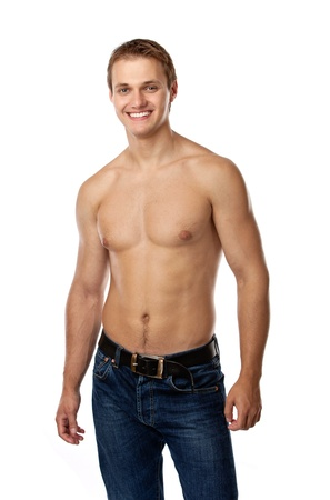 Cheerful young man in jeans with bare torso posing against a white background