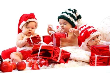 Foto de Three babies in xmas costumes playing with gifts over white background - Imagen libre de derechos