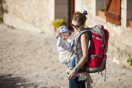 Foto de Young woman tourist carrying her little son in sling - Imagen libre de derechos