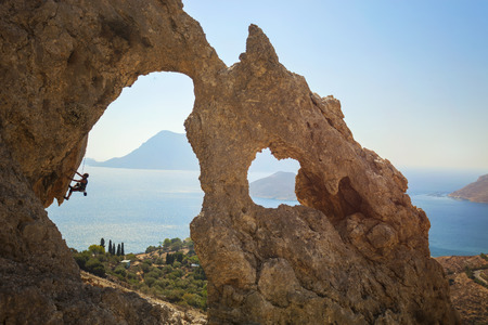 Senior female rock climber on a cliff. Kalymnos Island, Greece.