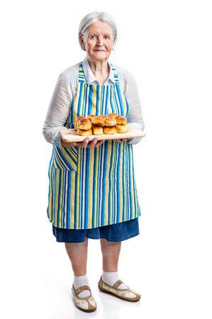 Photo for Senior woman holding fresh buns over white - Royalty Free Image