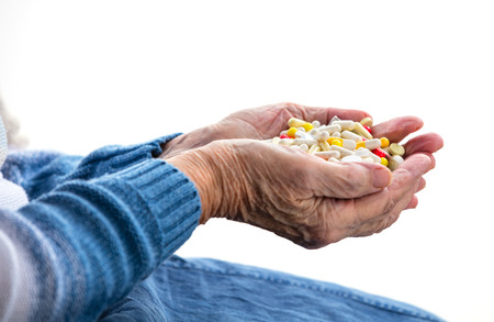 Cropped view of senior woman holding handful of pills over white
